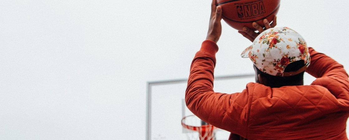 Baiat care arunca mingea de baschet NBA la cos
